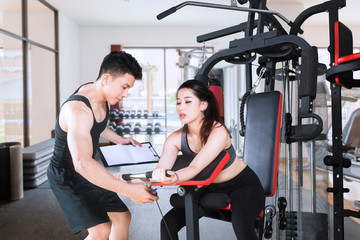 Young trainer helps his client to train in the gym