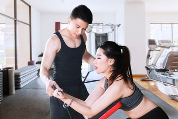 Young woman helped by trainer to exercise at gym