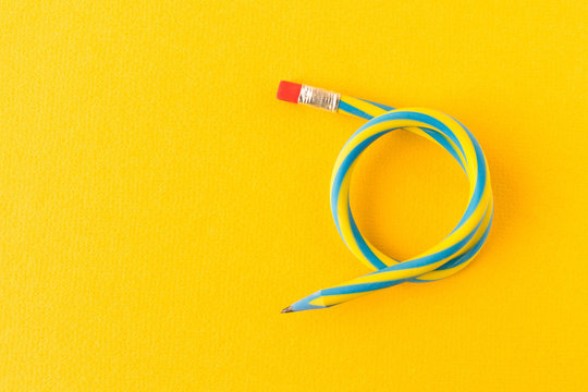 Flexible pencil . Isolated on yellow background. Bending pencil.