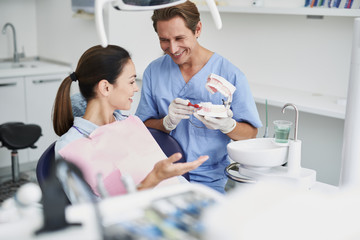 Smiling dentist showing teeth model to young woman