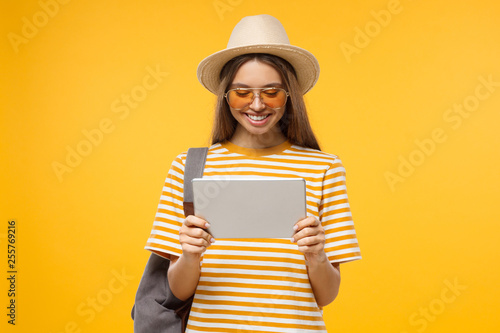 Happy smiling young woman tourist holding tablet pc, using online