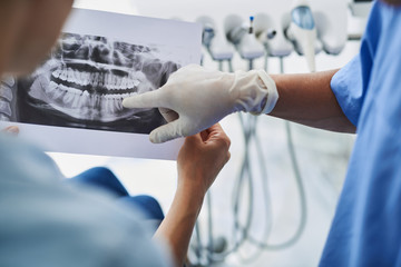 Young lady holding dental x-ray while dentist pointing at it