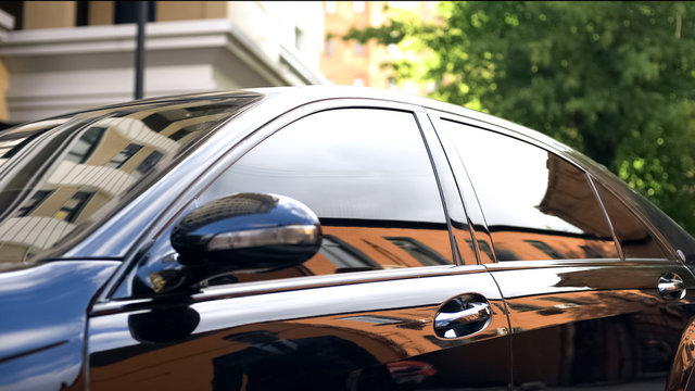 Luxury car with tinted glass standing at parking, reflection of businessman
