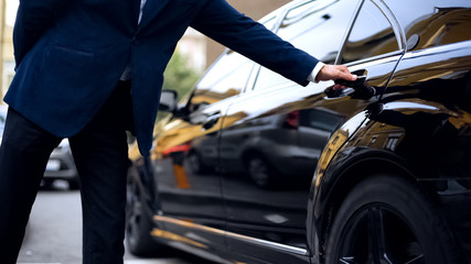 Personal driver opening backseat door in car for successful businessman, service