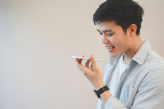close up young asian man holding smartphone and talking by use voice control function for call with others, lifestyle technology concept