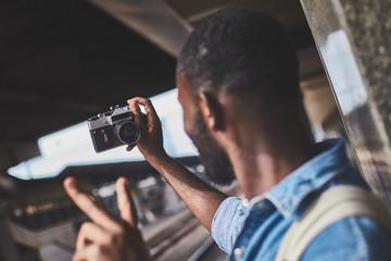 Male tourist taking selfie on retro camera