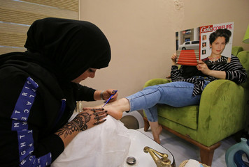 A woman applies henna to the feet of a customer inside her beauty shop in Basra