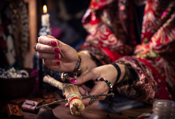 Gypsy female witch nailing the voodoo doll