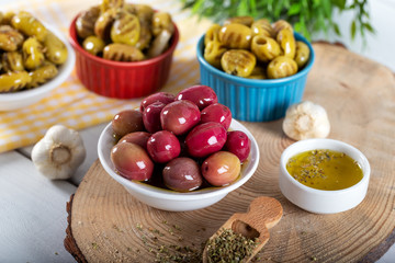 Green and red olives in bowl with olive oil and spices on wooden background