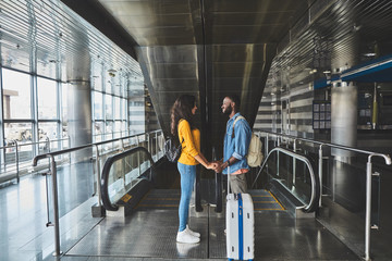 Full length of a loving couple standing at the airport