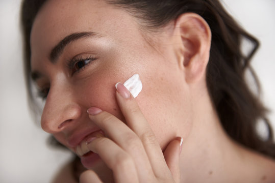 Close up of happy smiling woman applying cream