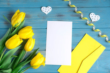 Mock up blank paper and envelope on blue wooden background with natural flowers of yellow color. Blank, frame for text. Greeting card design with flowers. Tulips on wooden background. View from above