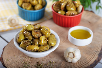 Wooden background with green olives, olive oil, garlic and spices