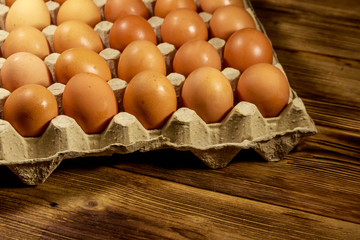 Raw chicken eggs in cardboard pack on wooden table