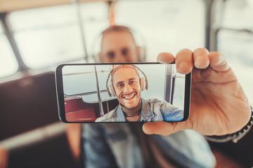 Portrait of happy man in headphones in smartphone