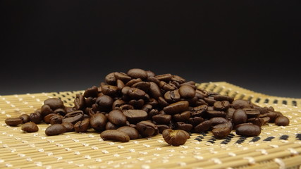 Roasted coffee beans over wood on black background