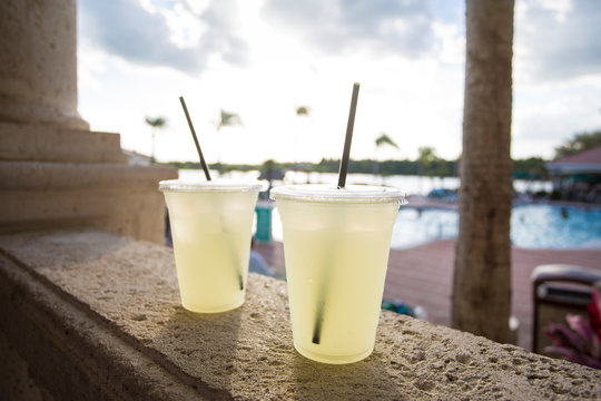 Two delicious glasses of lemonade poolside at a tropical outdoor resort. Selective focus on the two glasses on a hot summer day