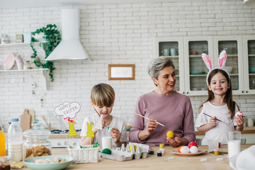 Waist up portrait of happy children and their grandmother coloring Easter eggs