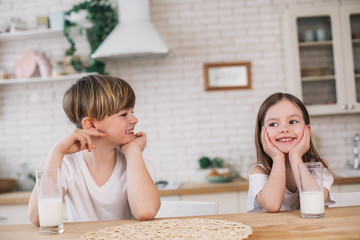 Half length of smiling children sitting at table in granny's house
