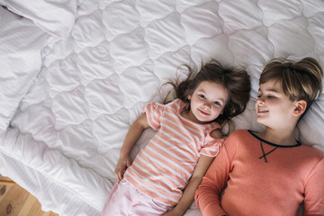 Top view of happy children lying on bed in granny's house