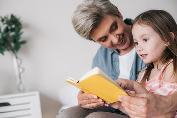 Side view of little girl reading book with her grandmother in house
