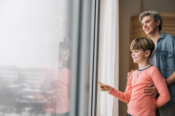 Waist up photo of smiling granny and her grandson at window