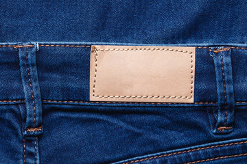 Brown leather empty copy space label texture. Back side of blue denim jeans trousers background.