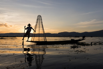 Traditional Burmese fisherman at Inle lake, Myanmar famous for their distinctive one legged rowing style