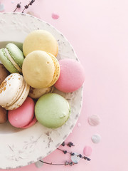 Delicious pink and green macaroons on pink paper, flat lay. Colorful macarons with confetti, candy bar for wedding on birthday. Stylish food Phone photo