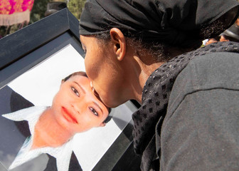 A woman kisses a portrait photo as she mourns during the burial ceremony of the Ethiopian Airline Flight ET 302 crash victims at the Holy Trinity Cathedral Orthodox church in Addis Ababa