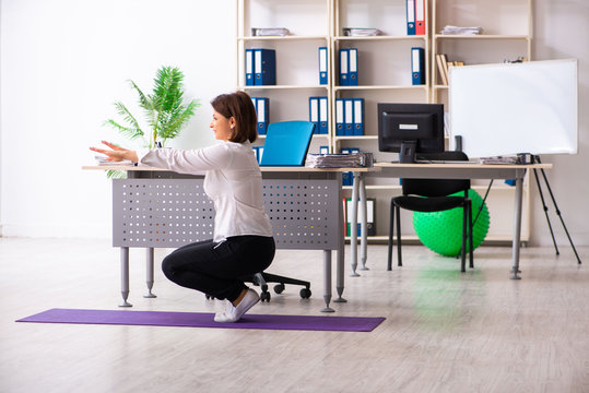 Middle-aged female employee doing exercises in the office