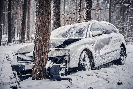 Front view of the car got into a skid and crashed into a tree on a snowy road.