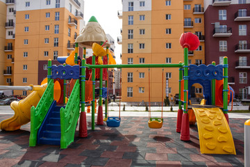 Children's playground with slides and swings in the courtyard of residential buildings.