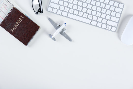Flat lay composition with airplane model and computer keyboard on light background. Travel agency concept
