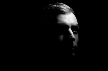 Dramatic portrait of a guy on a black background, black and white photography
