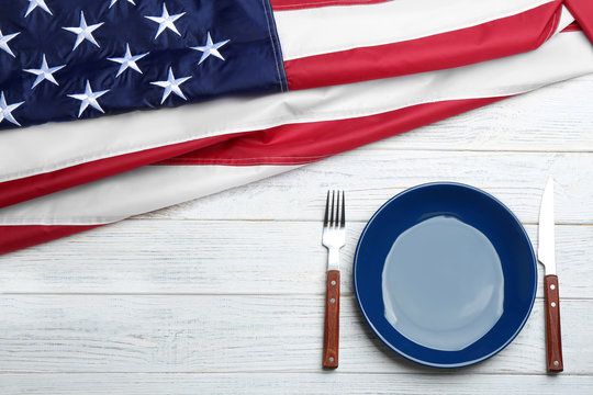 Patriotic table setting with USA flag on wooden background, flat lay. Space for text