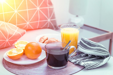 Croissants, black coffee, oranges and juice on the wooden tray. Breakfast in bed, sunny.
