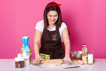 Happy housewife or baker wears kitchen apron dirty with flour, white t shirt, red headband, holds baking rolling pin and rolls out dough. Studio picture isolated over pink background. Baking concept.