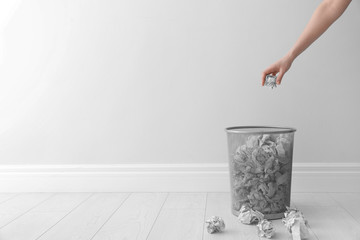 Woman throwing crumpled paper into metal bin against light wall. Space for text