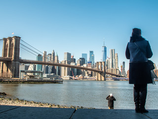 Young Woman by the river in Dumbo looking at Brooklyn Bridge and Cityscape of New York skyline.