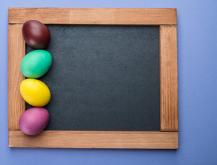 Blackboard and colorful Easter eggs around it. View from above.