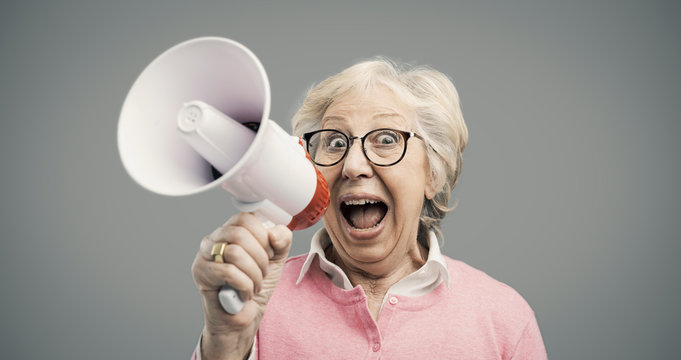 Cheerful senior lady shouting into a megaphone