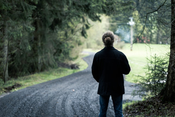 Young man smoking on road at end of dark forest