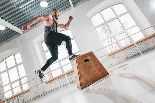 Strong man doing a box jump exercise at workout gym. Male athlete using box for crossfit exercises