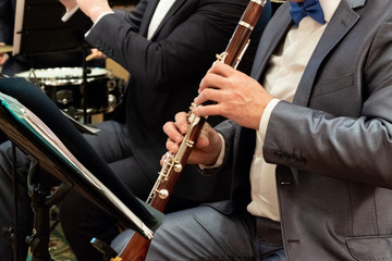 A man in a suit plays the clarinet. Brass band. Musical theme. Male fingers press the keys on the pipe. Close-up.