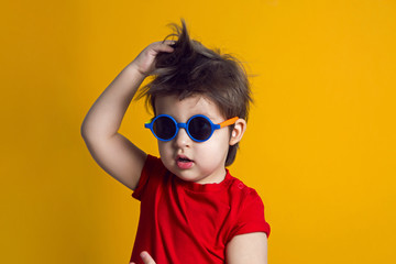 cheerful baby boy in red t-shirt stands