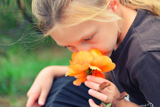 A cute and lovely squatting girl is smelling a yellow rose growing on a bush in the park.