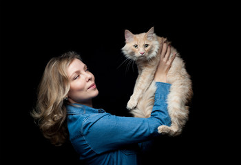 Beautiful proprietress posing with her cat on a black background