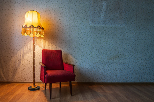 Old floor lamp and old armchair in a room.