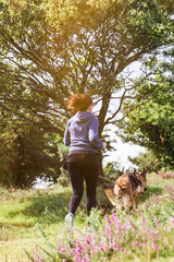 Young woman running with dog outdoor
